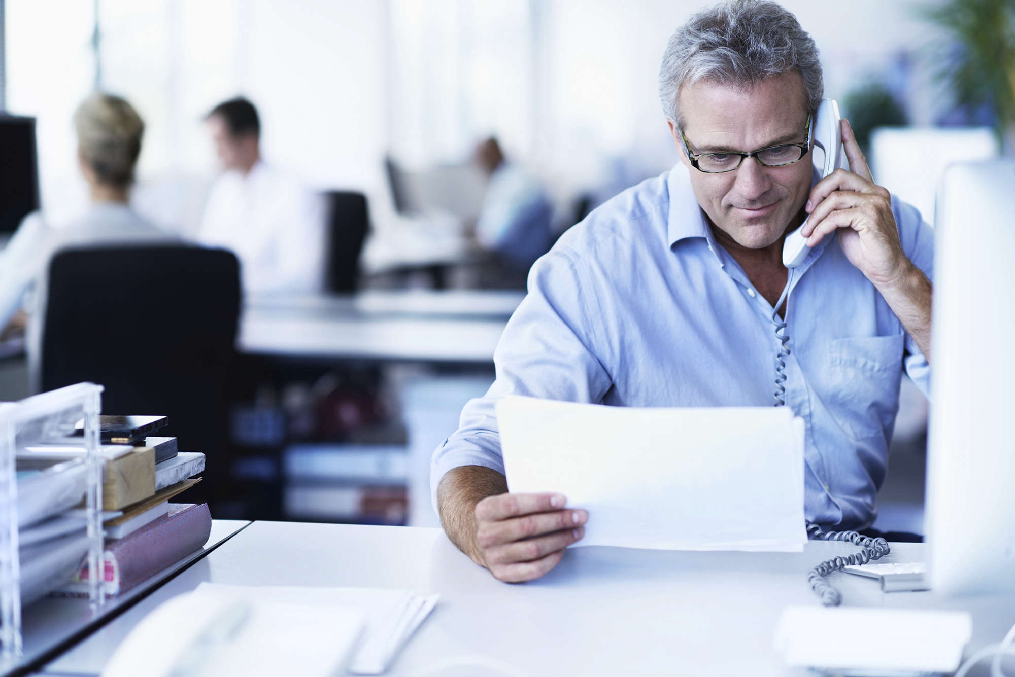 Shot of a mature businessman talking on a phone and reading a document while sitting at his desk in an office